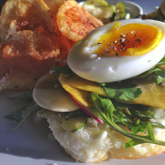 Soft-boiled egg biscuit sandwich with shaved vegetables, whipped herb butter, black garlic vinaigrette, chips, and pickles
