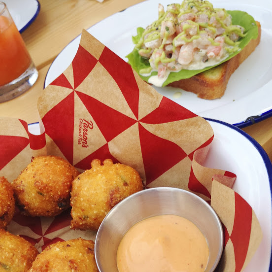 Hush puppies with ham hock, cream cheese, scallion, and harissa aioli; and shrimp toast with shrimp salad, creme fraiche, butter lettuce, and avocado