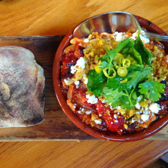 Baked egg with roasted peppers, chickpeas, guanciale, feta, and breadcrumbs