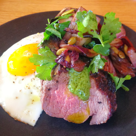 Marinated butcher's steak with squash polenta, charred radicchio, pepita pesto, and a fried egg