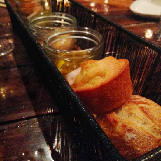 Bread basket with assorted breads, house pickles, honey butter, and tomato-herb oil