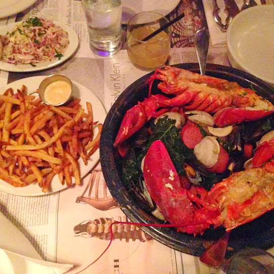"Clambake–style ""Dump Dinner""  with steamed clams, mussels, Maine lobsters, merguez sausage, kale, potatoes, fries, and slaw"
