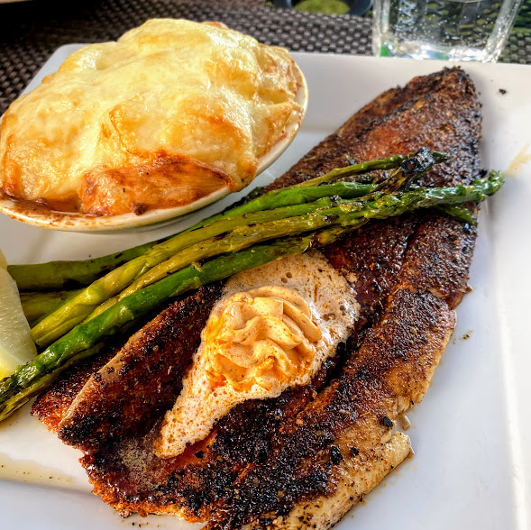 Blackened Baileys Harbor Fish Company Lake Michigan whitefish, New Orleans-style with spicy Cajun compound butter, au gratin potatoes, and asparagus, Harbor Fish Market & Grille