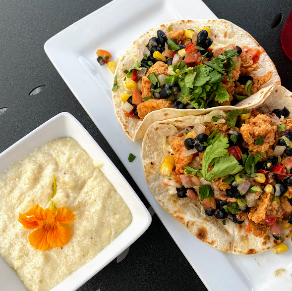 Alligator tacos with cajun fried gator, lemongrass slaw, chili sauce, roasted corn & black bean relish, and a side of goat cheese grits, The Fireside